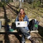 Kajsa med dator på en bänk i naturen